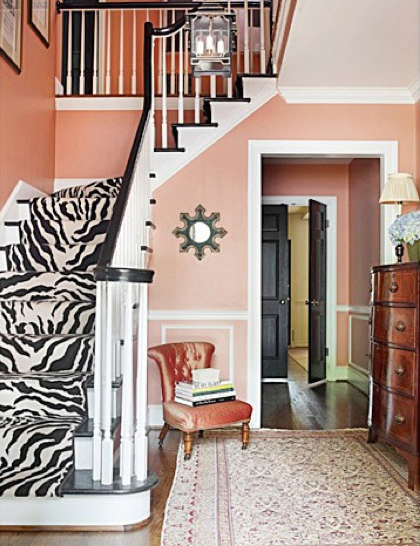 A peachy custom paint color provides the base for this rich foyer, accented with a Stark zebra rug runner and Oriental rug on the floor.