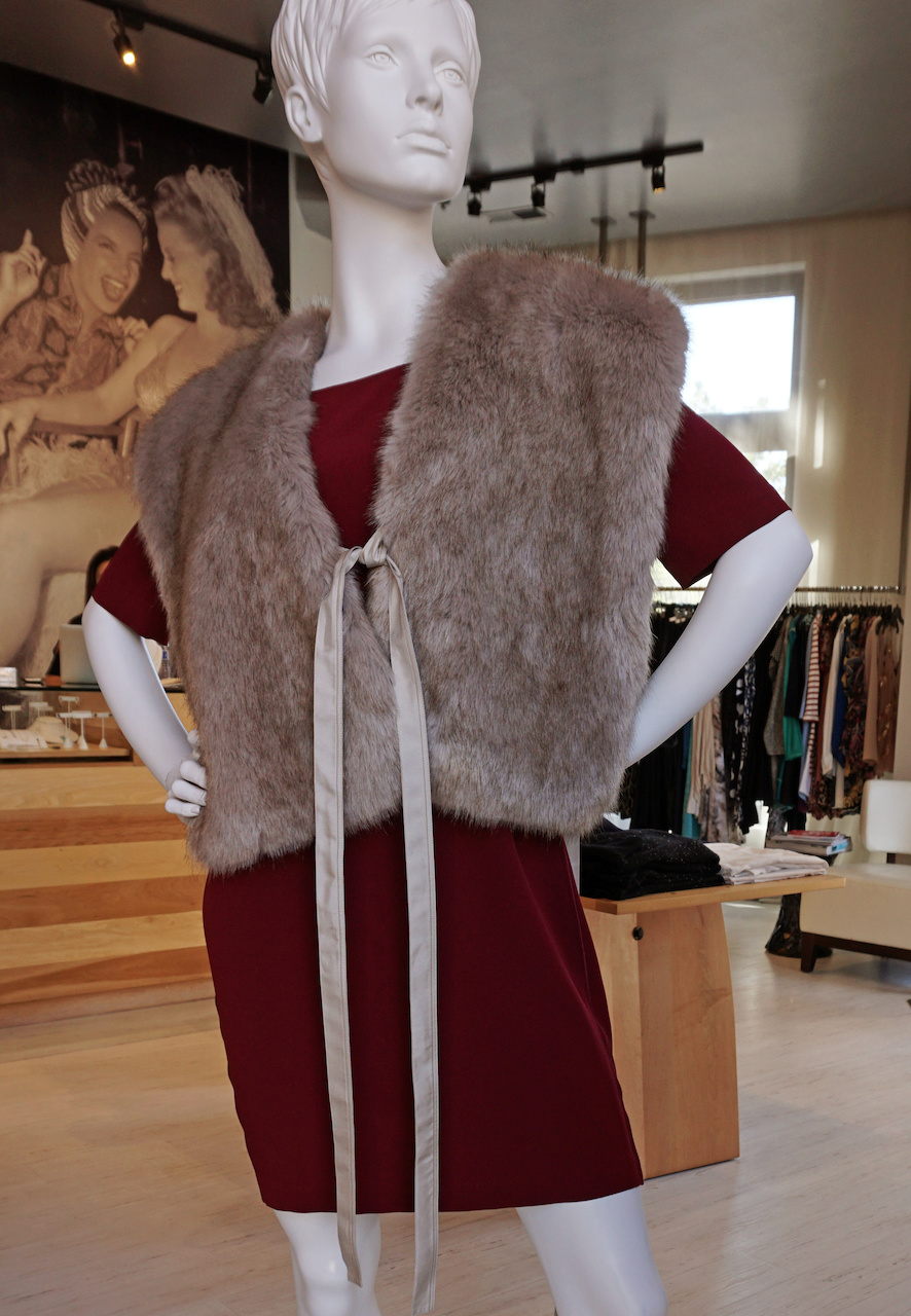 "From <a href=""https://styleblueprint.com/louisville/guide/peacock-boutique/"" target=""_blank"">Peacock Boutique</a>: Satin back cocoon dress, $495; Becken faux fur vest, $465"