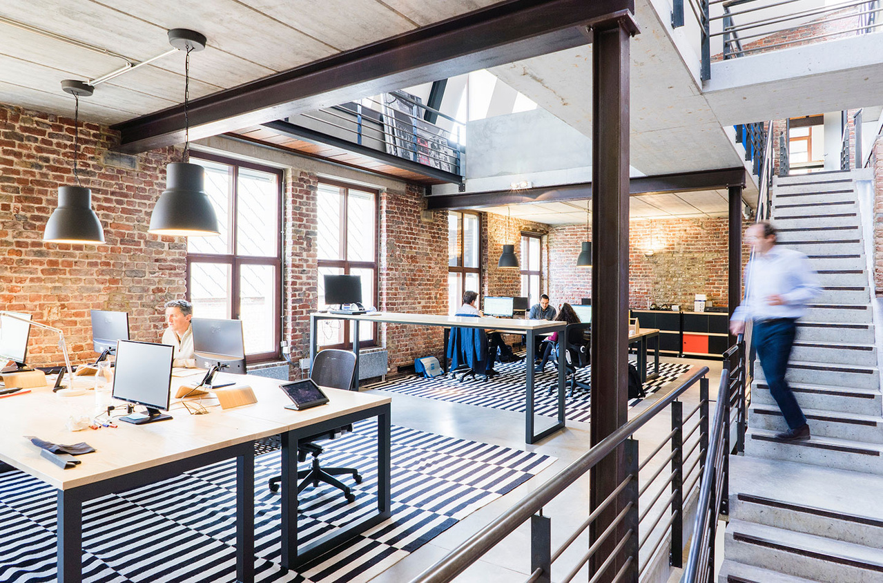 Modern industrial-style office space with brick walls and stairs