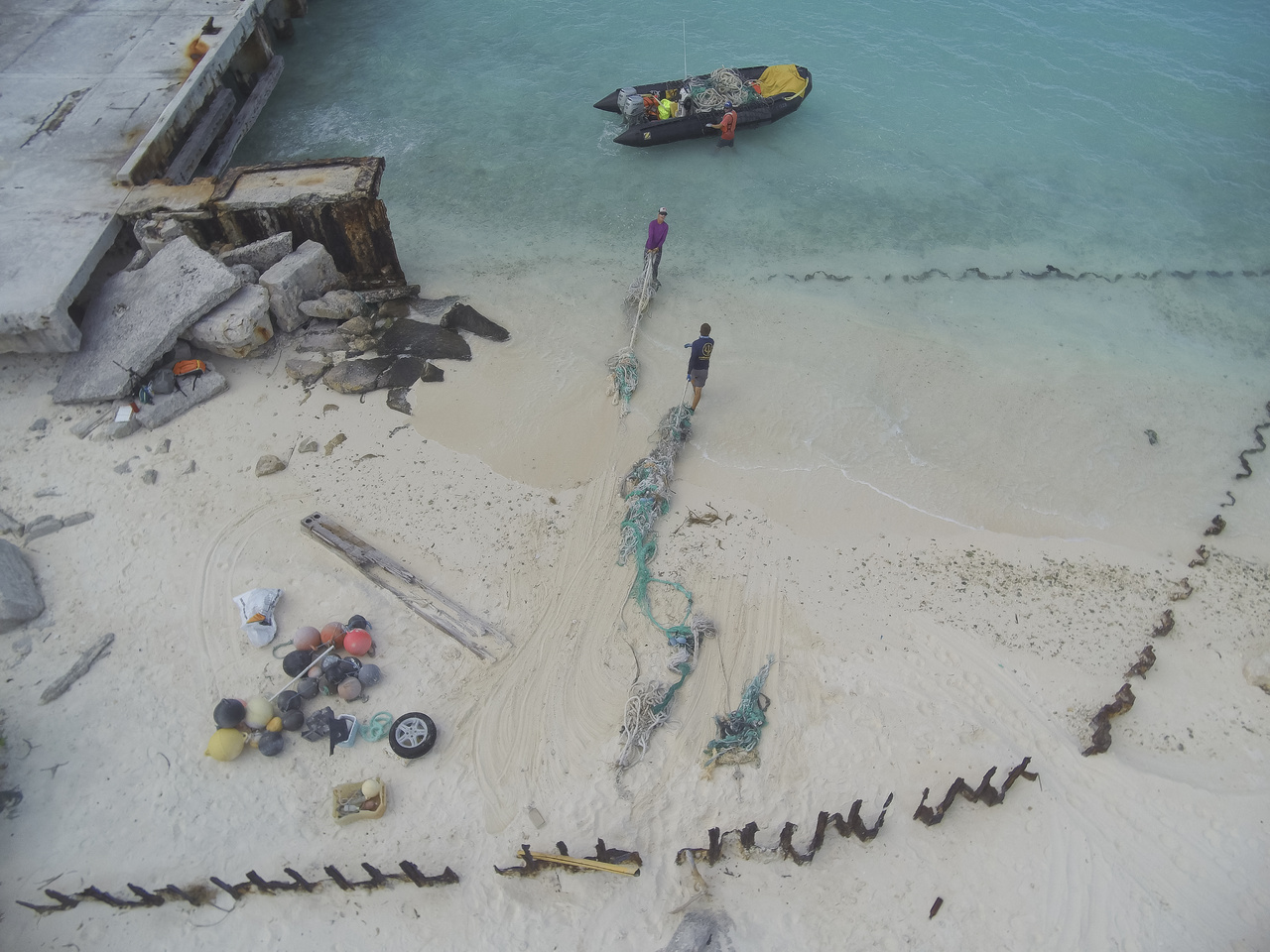 Removing the collected debris from the shorelines is the next step, and it is a task of its own. Scientists Kelley and Pamatat bring the fishing nets onto the small boat to transport them to the Sand Island, the main island of Midway Atoll. (Photo: NOAA Fisheries/Steven Gnam)