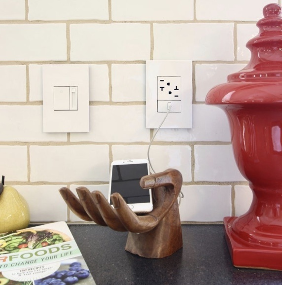 kitchen counter with magazine, charging phone and red sculpture