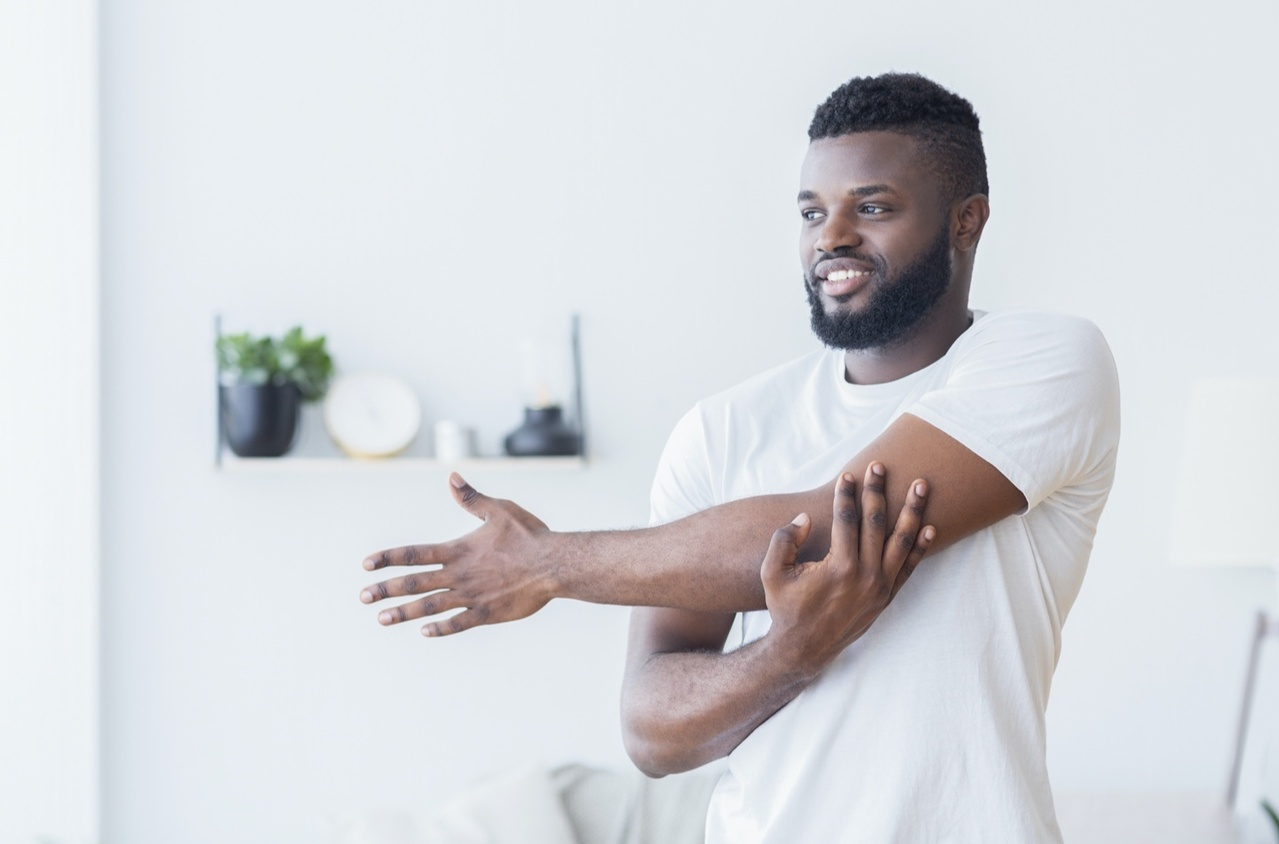 Man in white t-shirt stretching his arms