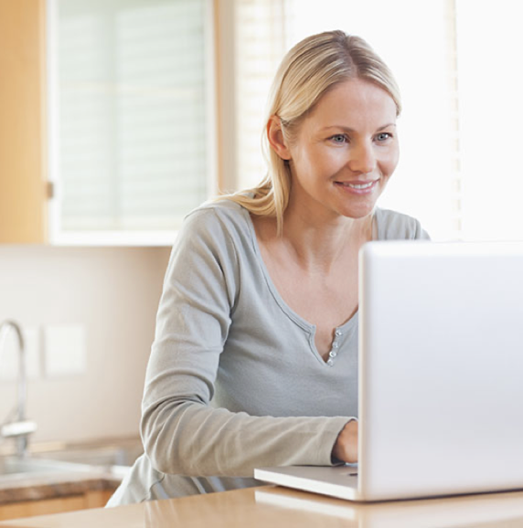 Woman with blonde hair smiling while using her laptop in her kitchen