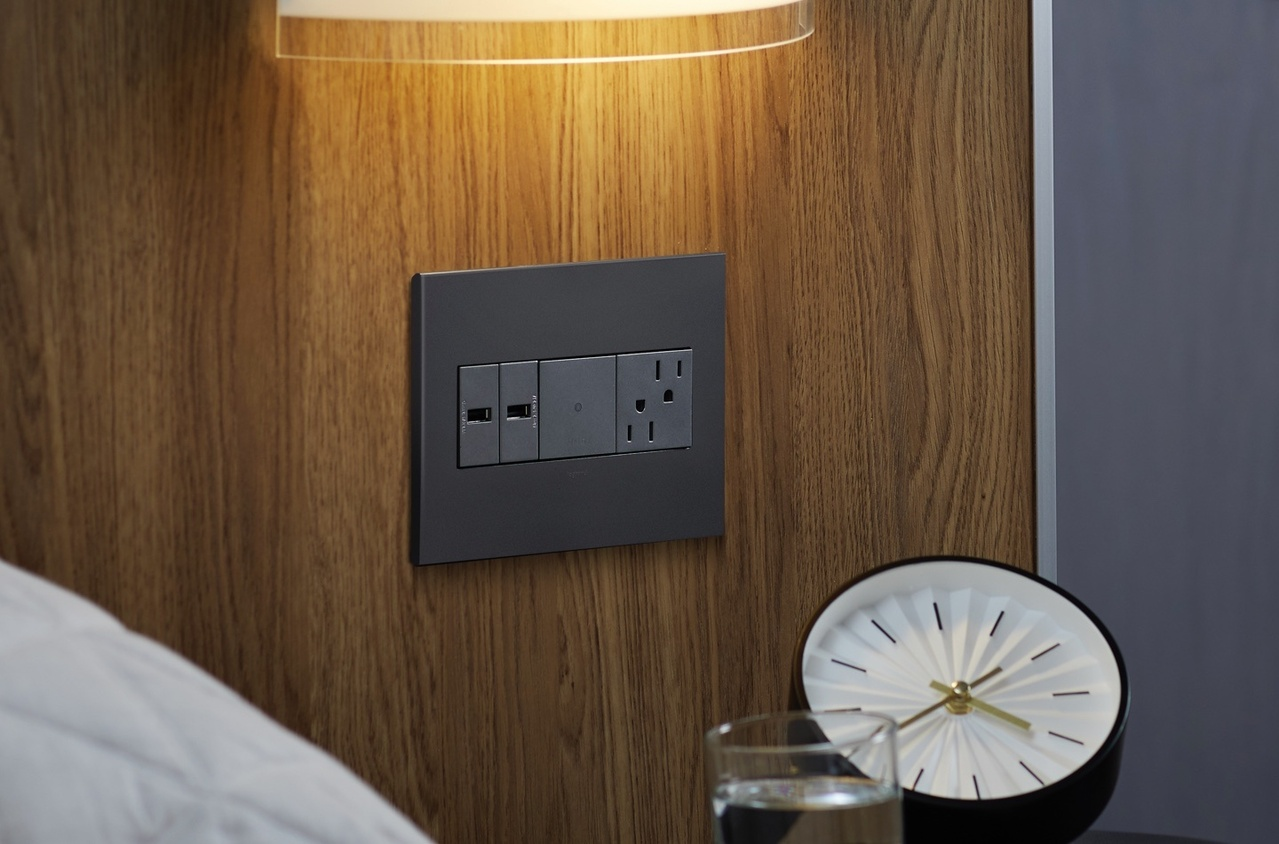 adorne magnesium outlets, switches, and USB receptacles built into wooden bed frame above a clock and glass of water