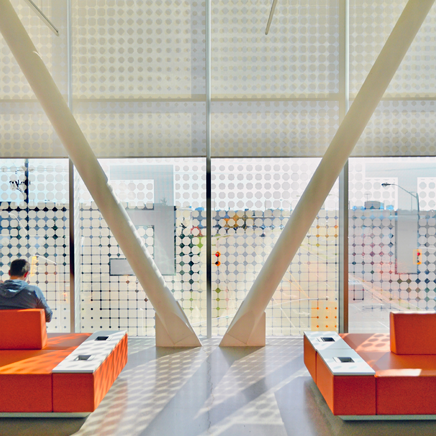 Man sitting on orange lobby seat looking out the window