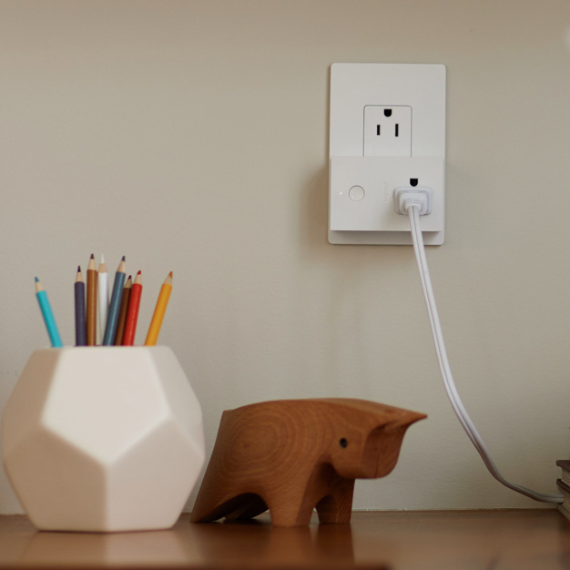 radiant smart plug-in switch in white radiant outlet by desk