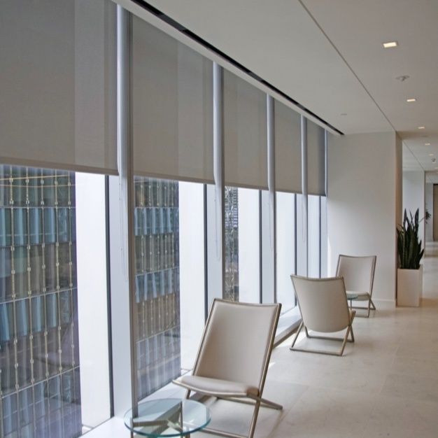 Manual roller shades on windows in a hallway of an office building