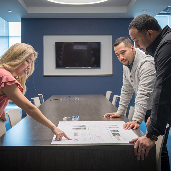 woman showing two men something on paper in office