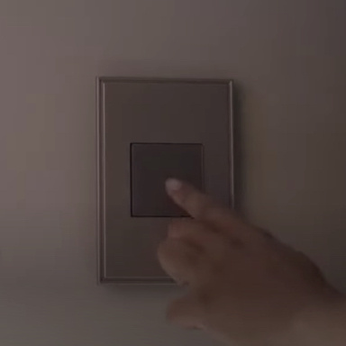 Hand touching magnesium light switch on gray wall