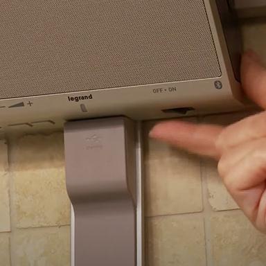 hand using speaker module of adorne Collection under cabinet lighting system