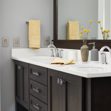 black bathroom vanity with white counters and blue and yellow accents
