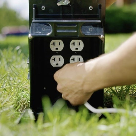 Outdoor ground box installed in grass with hand plugging in to one of four outlets