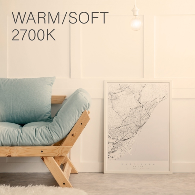 Wooden couch with blue cushions against a white wall and warm overlay