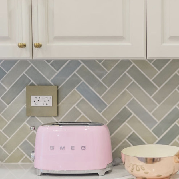Brass wall plate and white outlets next to retro pink toaster against green backsplash