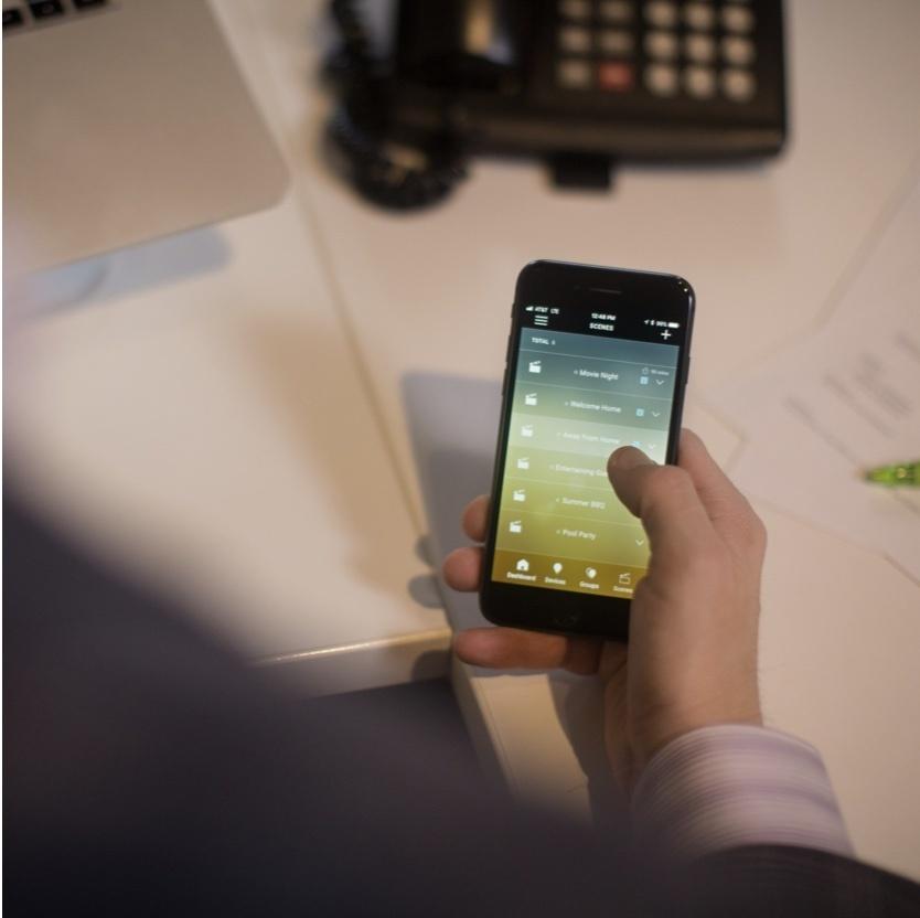 hand using smart phone displaying Legrand Smart Lights app
