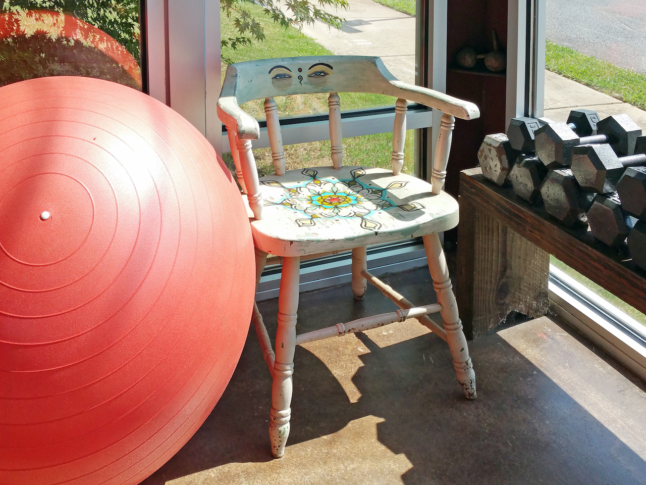 A corner of the sunroom features a colorfully decorated yoga lover's chair.