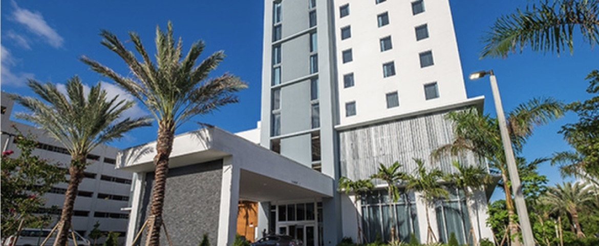 Front entrance driveway of AC Hotel Miami with palm trees