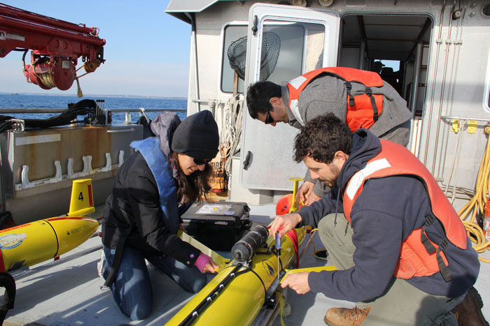 Tammy Silva and Benjamin Hodges (WHOI) and Eric Matzen (NEFSC) prepare a glider for deployment. Credit: Christopher McGuire/TNC.