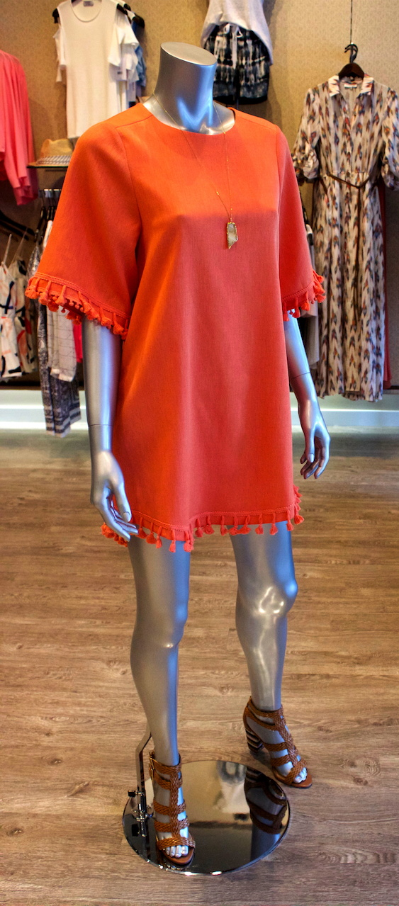 A bold orange dress with tassels is simple yet stunning, and a great choice for a modern Derby look