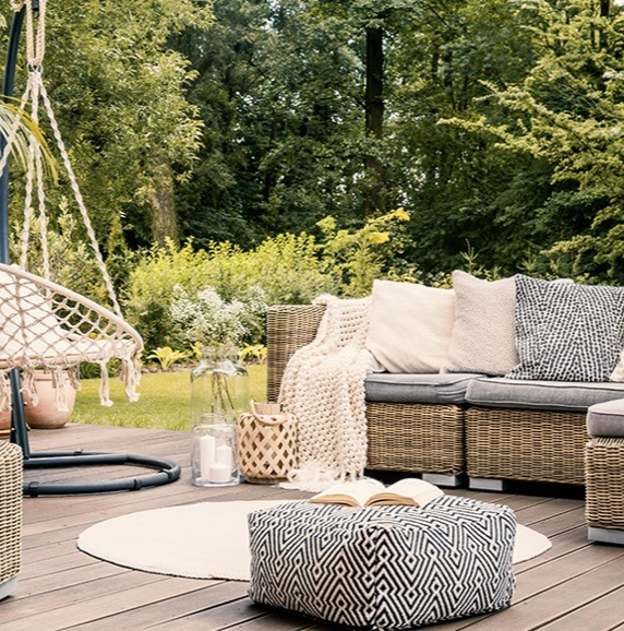 outdoor patio with wicker furniture and gray cushions