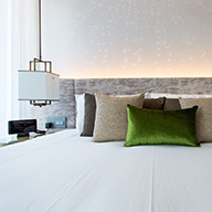 White bed with brown and green throw pillows