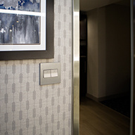 Hotel doorway with light switches and gray patterned wall paper