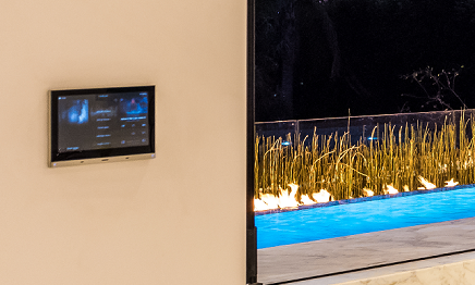Vantage control touchscreen mounted on beige wall near an open glass door leading to a pool