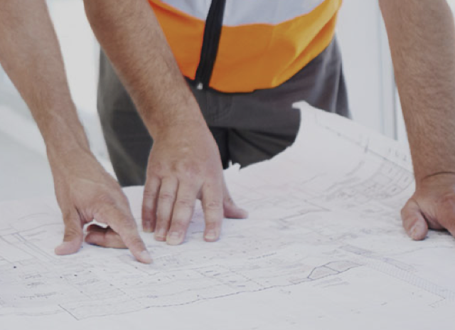 construction worker pointing at blueprints
