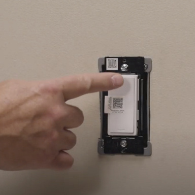 hand touching white switch in wall without wall plate