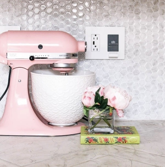 Pink Mixing bowl and pink flowers on countertop next to white wireless in wall charger and tile