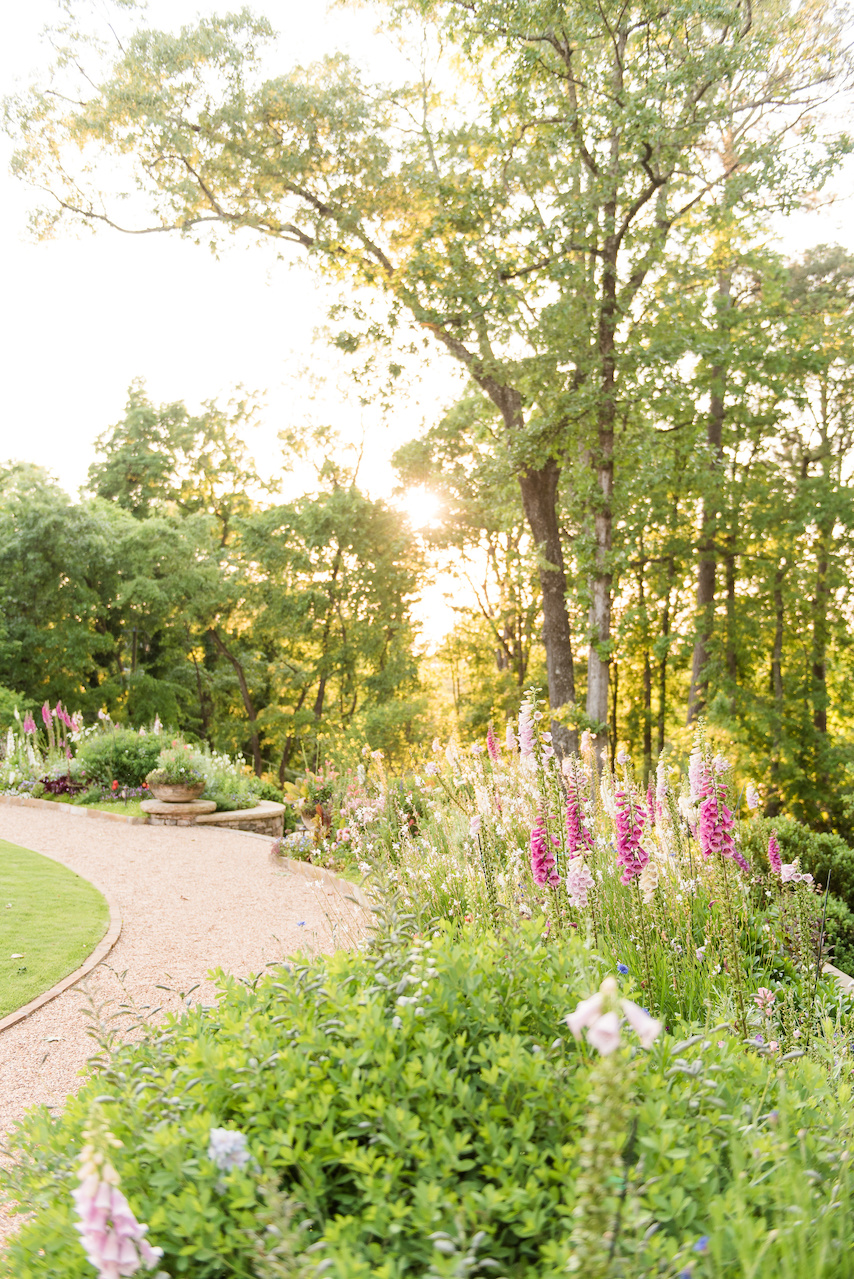"""""""Several ideas were proposed for the rear garden area in the initial phases that ultimately concluded with the sweeping curved retaining wall, allowing for a large open space off the main body of the house,"""" says John Wilson of Golightly Landscape Architecture. """"So, it worked well to have the flower border following the wall."""""""