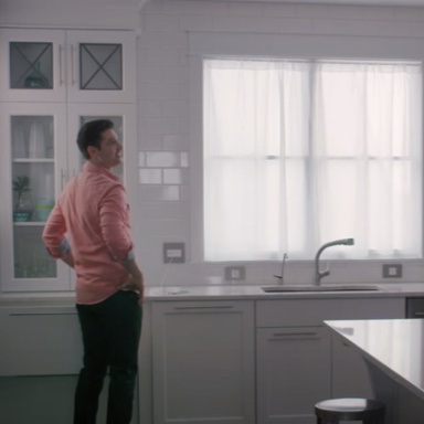 Man with hands on his hips in white kitchen