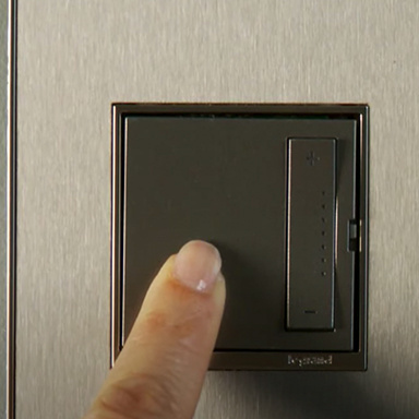 hand using adorne Collection sofTap dimmer switch in Magnesium