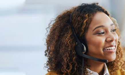 Customer service representative smiling and wearing a headset