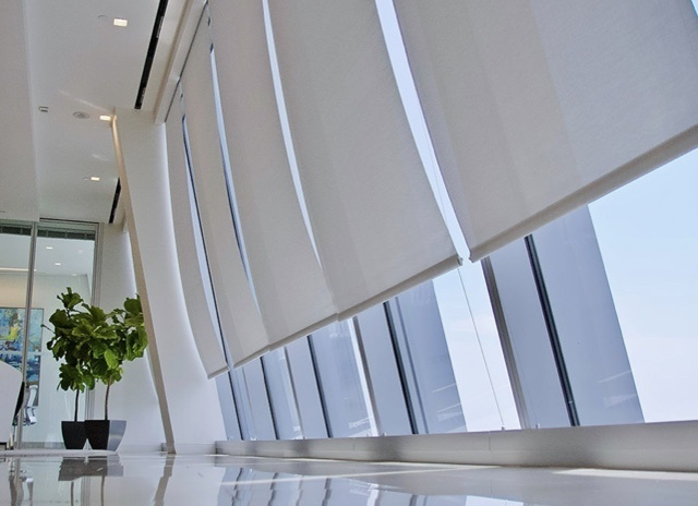 Several windows in a commercial office building with motorized shades