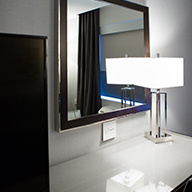 White hotel desk with large mirror above