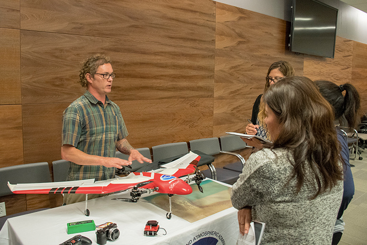 NOAA staff presenting drone technology/equipment to map coral reefs.