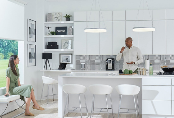 Woman sitting and man standing in kitchen talking and eating broccoli