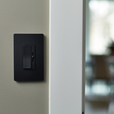 Black dimmer switch on beige wall by white door