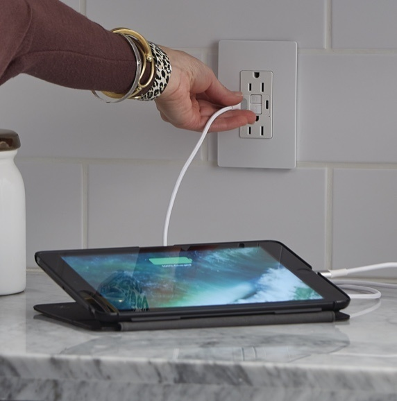 person plugging their tablet into the radiant Collection GFCI USB outlet to charge