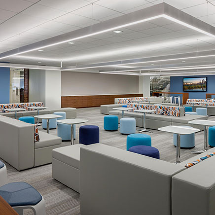 Large commercial space common area with overhead rectangular suspended lighting fixtures
