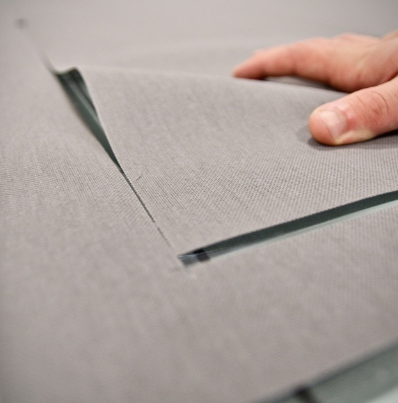 A person's hand folding over gray shading fabric