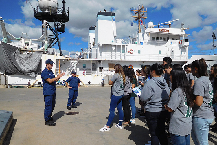 Two NOAA Corps officers giving a tour to students on a NOAA ship.