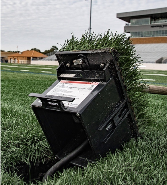 Outdoor ground box installed in grass with football field in background
