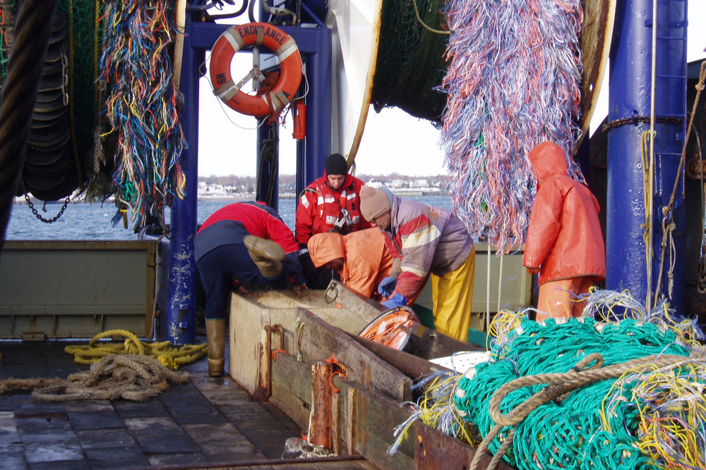 crew working with nets on fishing vessel