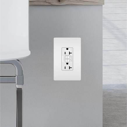 White GFCI outlet installed near pipe in grey wall