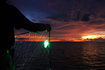 Fishermen prepare to set out nets with green LED lights attached. Sunset in background.