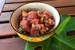 Bowl of 'ahi poke sitting on a Monstera leaf on a table.