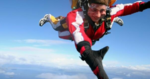 Andrew skydiving high above the Earth surrounded by blue skies and clouds.