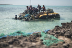 The team pulls a large mass of nets into the boat near the barrier reef at Midway Atoll.